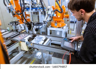 Engineer setting up automatic robot arms in smart factory, automotive industry, industrial concept