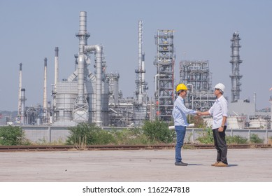 engineer shaking hands at construction and refinary oil