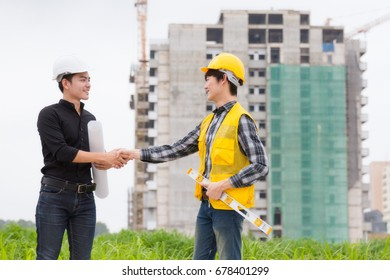 Engineer shaking hands other hand he is holding a helmet at construction site.