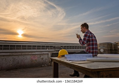 Engineer sitting alone and relax by  smoking on roof top after work at sunset with beautiful sky.