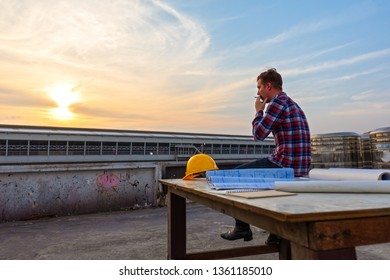Engineer sitting alone  and smoking on roof top after work at sunset with beautiful sky.