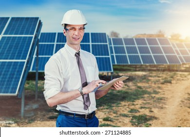 Engineer at solar power station with solar panel tablet checks. Practical lessons on renewable energy power plants.