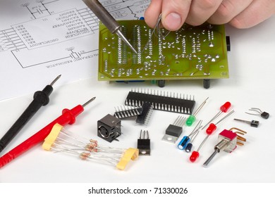 Engineer soldering circuit board surrounded by spare components