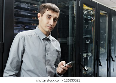 The engineer stand in datacenter near telecomunication equipment with smartphone.