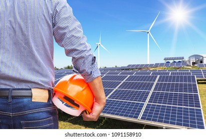 Engineer stand holding safety yellow helmet with solar cells and wind turbines generating electricity in hybrid power plant systems station use renewable energy to generate electricity
