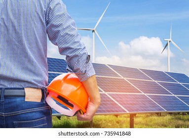Engineer stand holding safety yellow helmet with solar cells and wind turbines generating electricity in power station site alternative renewable energy from natural