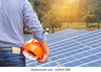 engineer stand holding yellow construction helmet with solar cells power station   renewable energy concept