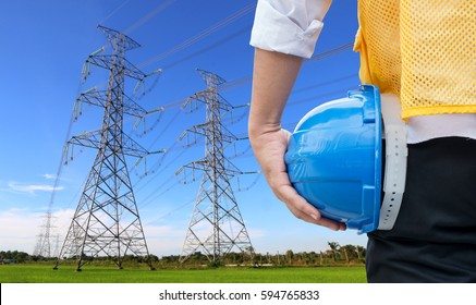 Engineer standing at electricity station, electric pole or high voltage with blue sky background.