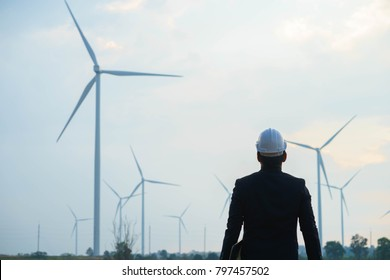 Engineer standing and hoding laptop with wind turbine.