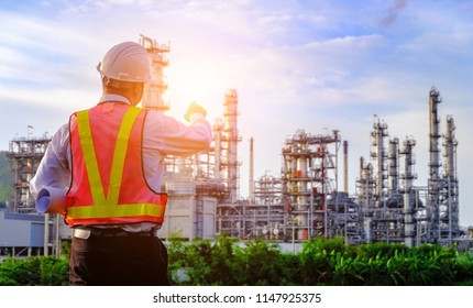 The engineer is standing on large industry background. The construction manager on the industry background.
