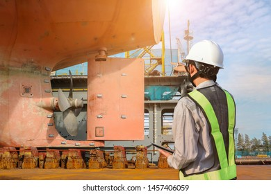 Engineer standing pointing to the target of working, Big ship under Repairing of Propeller with rudder at stern ship, surveyor, inspecting the final on dry dock in shipyard Thailand.