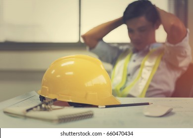 Engineer stress holding his head with hands sitting at the table in the office