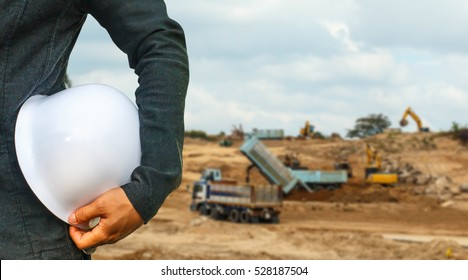 engineer suit white helmet for security stood on the details of Excavator and grader working at construction site.