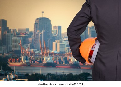 engineer in suite holding helmet and blue ships in harbor background