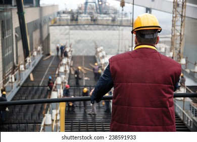 Engineer supervising workers from platform