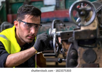 Engineer or supervisor wearing safety glass and glove, concentrate on adjusting the gap of the milling (lathe) machine at the iron manufacturing factory. Heavy sweating on his face. Industrial area.