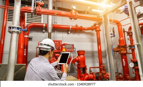 Engineer with tablet check red generator pump for water sprinkler piping and fire alarm control system.