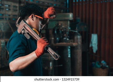 Engineer taking a break while working and wiping perspiration from his head with his safety gloves while holding a pipe wrench