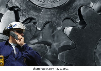 engineer talking in phone with giant gears machinery in background