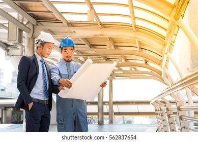 Engineer talking to a worker in city background