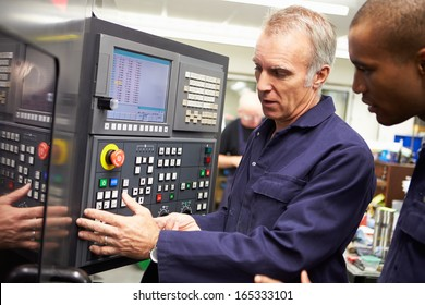 Engineer Teaching Apprentice To Use Computerized Lathe