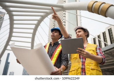 Engineer team of smart Asian man and beautiful American woman check project plan from digital tablet and paper blueprint . International team to work at construction site in city. Success Teamwork