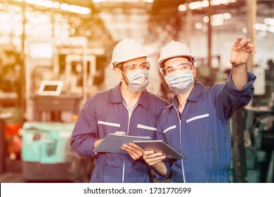 Engineer teamwork worker wearing disposable face mask or face shield during working in factory to prevent Covid-19 virus air dust pollution and for good hygiene.