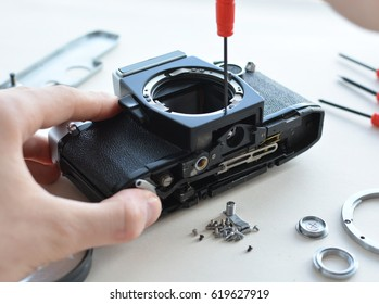 Engineer technician checks optics and carry out maintenance and cleaning of the broken camera at the service center. Top view of the workplace and the hands of the engineer.
