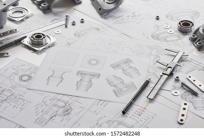 Engineer technician designing drawings mechanicalparts engineering Engine manufacturing factory Industry Industrial work project blueprints measuring bearings caliper tools - Shutterstock ID 1572482248