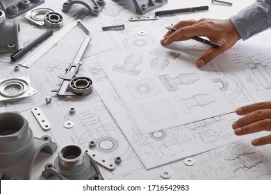 Engineer technician designing drawings mechanical parts engineering Engine 				manufacturing factory Industry Industrial work project blueprints measuring bearings caliper tool.
