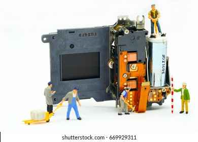 Engineer and technician Minitures are fixing camera shutter assembly , Miniture workers  are checking  optics and carry out maintenance and cleaning of the broken camera at the service center.