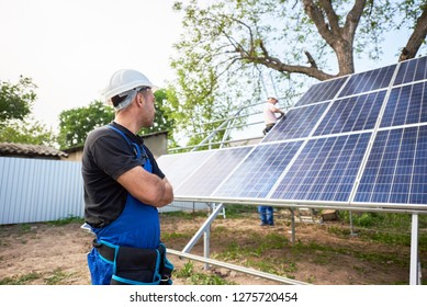Engineer technician standing in front of unfinished high exterior solar panel photo voltaic system blue shiny surface with team of workers on high platform.