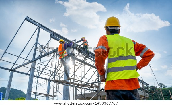 Engineer technician watching team of workers on high steel platform,Engineer technician Looking Up and Analyzing an Unfinished Construction Project.