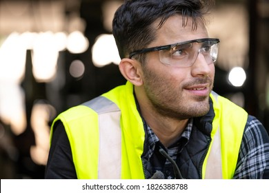 Engineer or technician wearing safety glasses and vest sitting on the floor and relax in the metalworking factory. He is looking away. Relaxation and industrial concept.