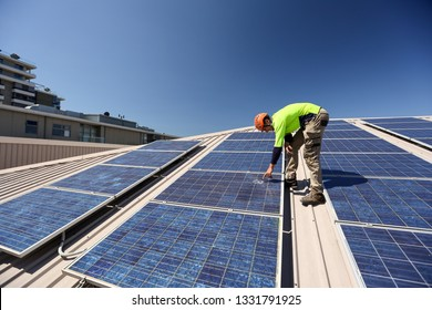 Engineer technician wearing a safety helmet long sleeve shirt conducting safety inspecting roof power sola cell damage glass panel  building site Sydney, Australia