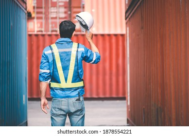 Engineer or technician wears jeans blue jacket and reflective cloth put walkie talkie in jeans pocket, he is taking white hard hat off standing in between cargo container. Engineering work concept.