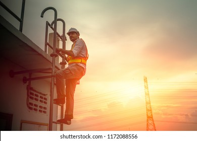 engineer technician working at ladder to fix electricity cable line sunset background