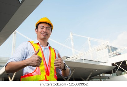 Engineer thump up and smile,Portrait of Asian engineer on site background,Good job