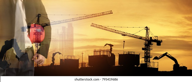 engineer and tower cranes at construction site and city background