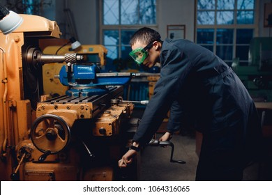 Engineer turner Asian man stands in goggles behind an automatic drilling machine. Concept industrial worker for the production of metal structures.