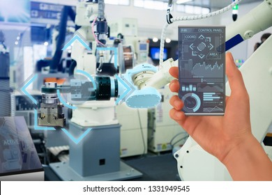 Engineer uses a futuristic transparent smartphone to control robotic arm. Smart industry 4.0 concept.