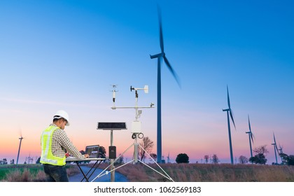 Engineer using laptop computer collect data with meteorological instrument to measure the wind speed, temperature and humidity and solar cell system on wind turbine station, Smart agriculture concept