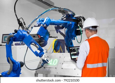 Engineer using laptop computer control laser robotic cutting on metal plate, Industry 4.0 concept