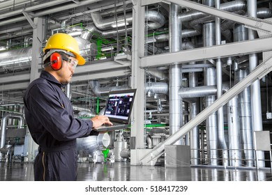 Engineer using laptop computer for maintenance equipment and pipeline system in thermal power plant factory