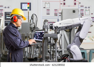 Engineer using laptop computer for maintenance automatic robotic hand machine tool in automotive industry