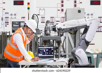 Engineer using laptop computer for maintenance automatic robotic hand machine tool at industrial, Industry 4.0 concept