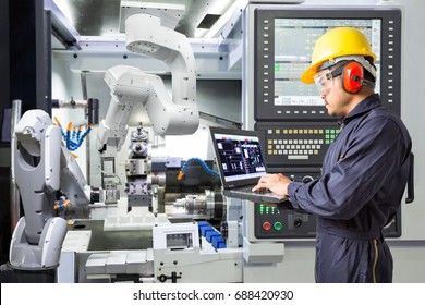 Engineer using laptop computer for maintenance automatic robotic industrial with CNC machine in smart factory. Industry 4.0 concept