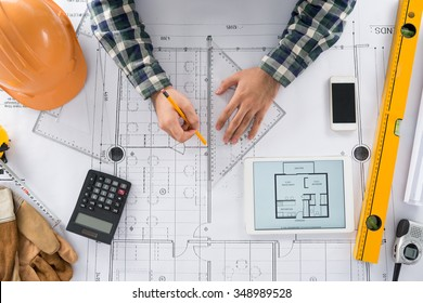 Engineer using set square to draw a line on the blueprint