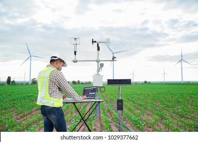 Inženýr pomocí tabletového počítače shromažďovat data s meteorologickým přístrojem pro měření rychlosti větru, teploty a vlhkosti a systému solárních článků na pozadí kukuřičného pole, inteligentní koncepce zemědělství