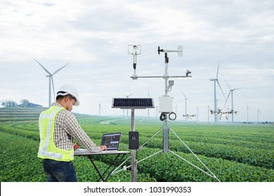 Engineer using tablet computer collect data with meteorological instrument to measure the wind speed, temperature and humidity and solar cell system on green tea field, Smart agriculture concept